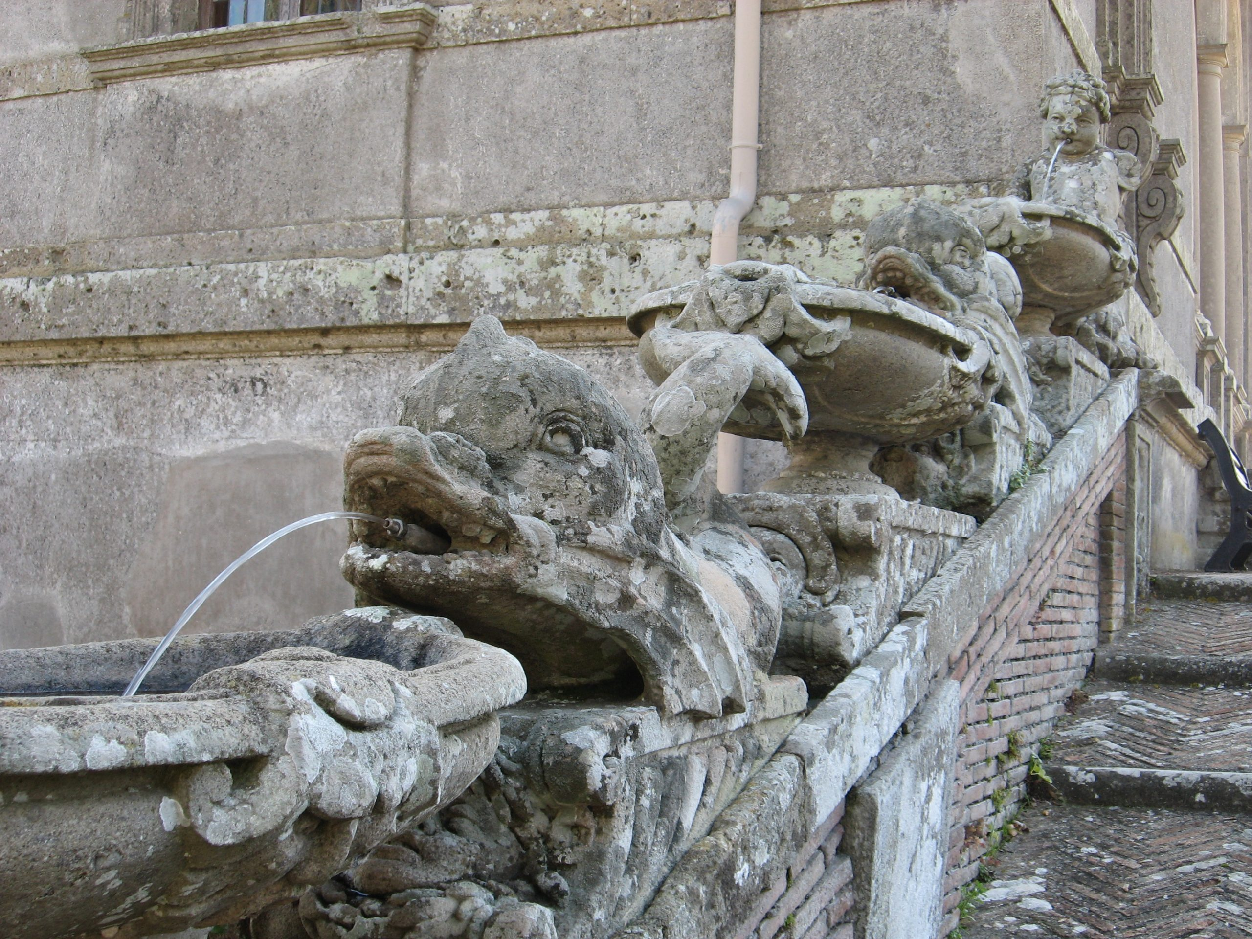 detail of a fountain at palazzo farnese: water cascading from the mouths of stone dolphins lining a flight of steps