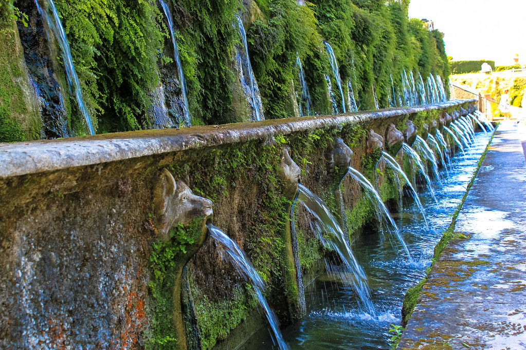 a detail of the playful water feature called the 100 fountains, each spout comes out of a gorgony face